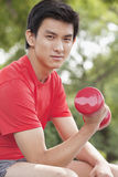 Young Man exercising with Dumbbell Stock Photo