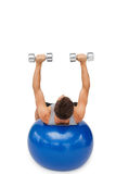 Young man exercising with dumbbells on fitness ball Royalty Free Stock Photography