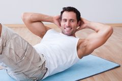 Young Man Exercising On Exercise Mat Stock Photography