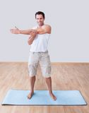 Young Man Exercising On Exercise Mat. Indoors Royalty Free Stock Photos