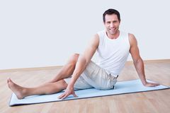 Young man exercising on exercise mat. Indoors Stock Photography