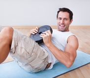 Young man exercising on exercise mat. Indoors Stock Photos