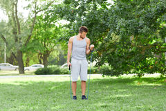 Young man exercising with expander in summer park Stock Images