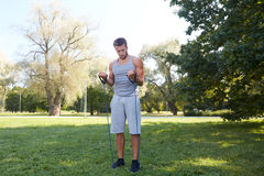 Young man exercising with expander in summer park Royalty Free Stock Photos