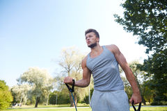 Young man exercising with expander in summer park. Fitness, sport, exercising, training and lifestyle concept - young man exercising with expander in summer park Stock Photography