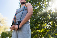 Young man exercising with expander in summer park Royalty Free Stock Photography