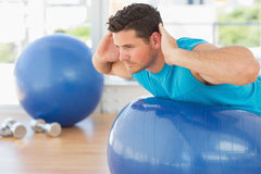 Young man exercising on fitness ball at a bright gym Royalty Free Stock Photo