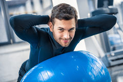 Young man exercising on fitness ball at gym Stock Photo