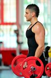 Young man exercising in the gym Stock Images