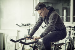 Young man exercising in gym: spinning on stationary bike Stock Photos