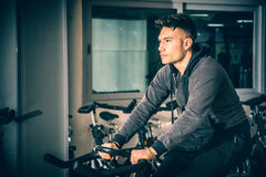 Young man exercising in gym: spinning on stationary bike Royalty Free Stock Photos