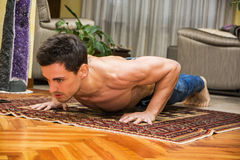 Young man exercising on his living room floor. Training by doing push-ups in a health and fitness concept Royalty Free Stock Image