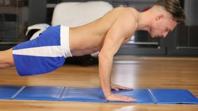 Young man exercising on his living room floor. Training by doing push-ups in a health and fitness concept stock video footage