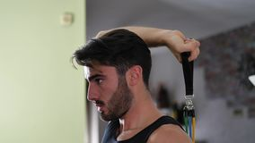Young man exercising at home with elastic bands. Young man exercising in his living room at home, training with elastic bands in a health and fitness concept stock footage