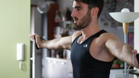 Young man exercising at home with elastic bands. Young man exercising in his living room at home, training with elastic bands in a health and fitness concept stock video footage