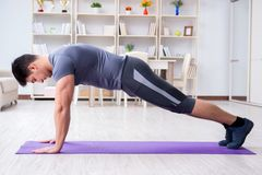 Young man exercising at home in sports and healthy lifestyle con Stock Image