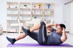 Young man exercising at home in sports and healthy lifestyle con Stock Photo