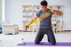 Young man exercising at home in sports and healthy lifestyle con Stock Photos