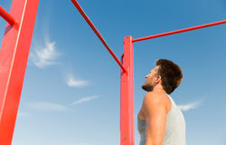 Young man exercising on horizontal bar outdoors Royalty Free Stock Photo