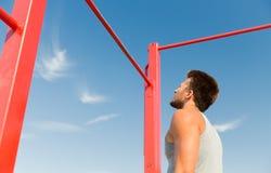 Young man exercising on horizontal bar outdoors Royalty Free Stock Photo