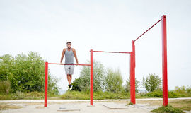 Young man exercising on horizontal bar outdoors. Fitness, sport, training and lifestyle concept - young man exercising on horizontal bar outdoors Royalty Free Stock Images