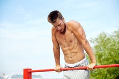 Young man exercising on horizontal bar outdoors. Fitness, sport, training and lifestyle concept - young man exercising on horizontal bar outdoors Stock Photo