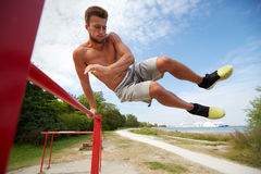 Young man exercising on horizontal bar outdoors Stock Images