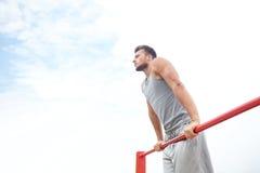 Young man exercising on horizontal bar outdoors Stock Photography