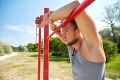 Young man exercising on horizontal bar outdoors Royalty Free Stock Images