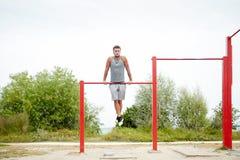 Young man exercising on horizontal bar outdoors Stock Photo