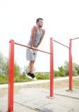 Young man exercising on horizontal bar outdoors Royalty Free Stock Image