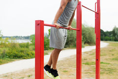 Young man exercising on horizontal bar outdoors Stock Image
