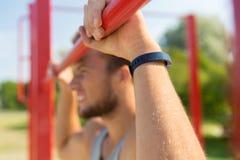Young man exercising on horizontal bar outdoors Stock Image