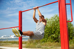 Young man exercising on horizontal bar outdoors Royalty Free Stock Photos