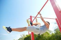 Young man exercising on horizontal bar outdoors Royalty Free Stock Photography