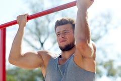 Young man exercising on horizontal bar outdoors Stock Images