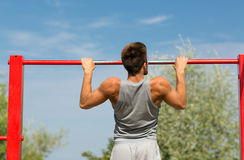 Young man exercising on horizontal bar outdoors. Fitness, sport, exercising, training and lifestyle concept - young man doing pull ups on horizontal bar outdoors stock photo