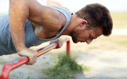 Young man exercising on horizontal bar outdoors. Fitness, sport, exercising, training and lifestyle concept - young man doing push ups on horizontal bar outdoors Stock Images