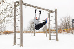 Young man exercising on horizontal bar in winter Stock Images