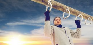 Young man exercising on horizontal bar in winter. Fitness, sport, exercising, training and people concept - young man doing pull ups on horizontal bar outdoors Stock Image