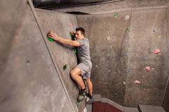 Young man exercising at indoor climbing gym. Fitness, extreme sport, bouldering, people and healthy lifestyle concept - young man exercising at indoor climbing stock images