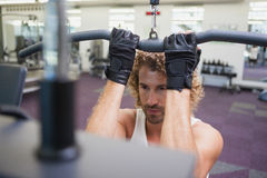 Young man exercising on a lat machine in gym Stock Image