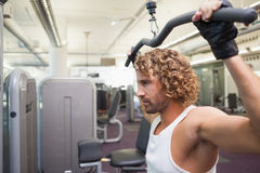 Young man exercising on a lat machine in gym Royalty Free Stock Images