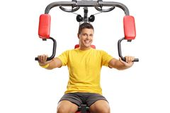 Young man exercising on a multifunctional machine Stock Photos