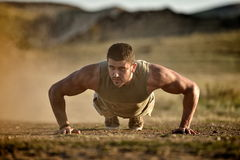 Young man exercising outdoor on dusty field Royalty Free Stock Photography