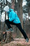 Young man exercising outdoors in a forest among leafless trees o Royalty Free Stock Photography