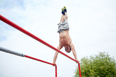 Young man exercising on parallel bars outdoors Royalty Free Stock Photos