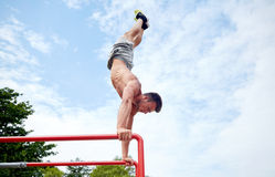 Young man exercising on parallel bars outdoors Stock Photo
