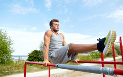 Young man exercising on parallel bars outdoors Royalty Free Stock Image