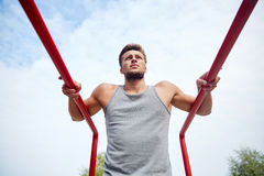 Young man exercising on parallel bars outdoors Royalty Free Stock Photography